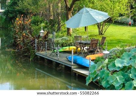 Table and chairs  on wooden balcony by the water in a garden