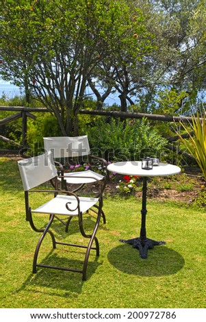 Table and iron chairs on green grass in garden with flowers, trees and sea view(Greece)