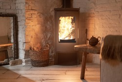 Table and teapot near wood stove fireplace in comfort house with cozy interior in room. Wicker basket with firewood near chimney with metal body and glass door