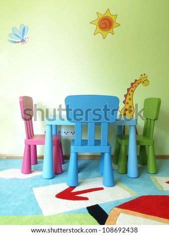 Table and three chairs in children's room