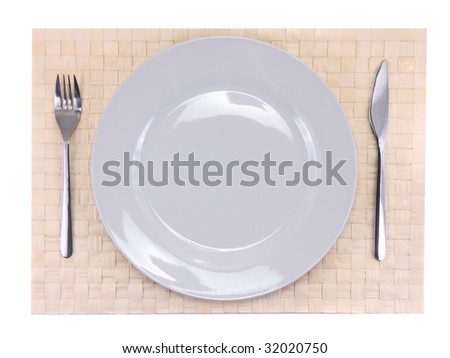 Table appointment-big plate,fork,knife on beige wicker bamboo mat. All around Isolated.