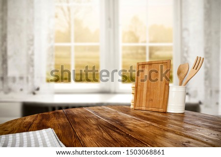 Table background of free space for your decoration and blurred background of window with autumn landscape