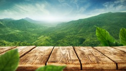 table background of free space for your decoration and blurred landscape of mountains.Blue sky with sun light and green small leaves.