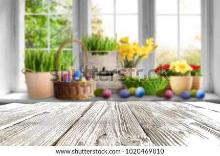 Table background of free space for your decoration and blurred window and easter decoration. Spring time background.