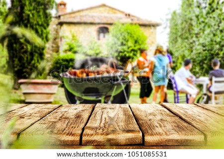 Table background of free space for your your decoration with blurred background with grill party and few people.