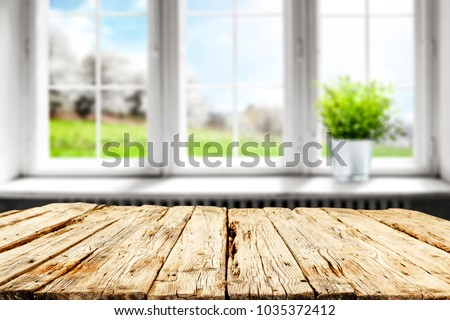Table background with free space for your decoration of product and blurred window with spring landscape and green plant on window sill.