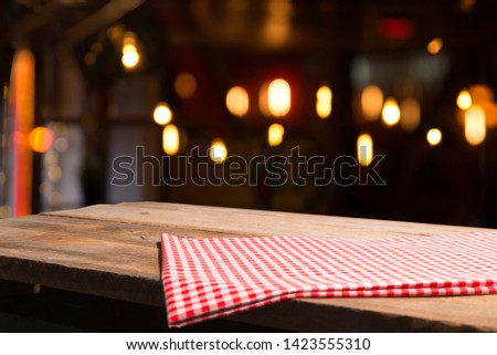 Table background with napkin and blurred bar background space #1423555310