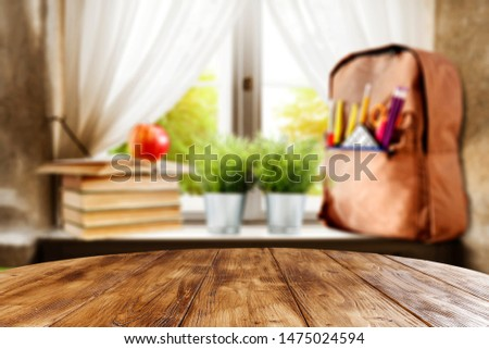 Table background with yellow schoolbag on a windowsill in the school interior.