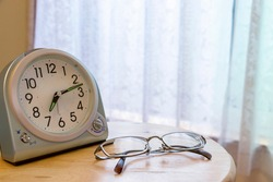 Table clock and eyeglasses on the table by the window, Letters on the clock mean