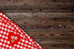 Table  cloth on wooden table rustic background. Copy space for text, mock up. Christmas or oktoberfest background with red heart with White Edelweiss  on fabric checkered tablecloth.