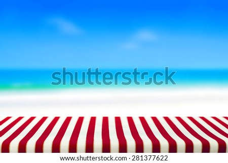 Table covered with striped tablecloth on blurred beach background, picnic and holiday concepts - can be used for display and montage your products
