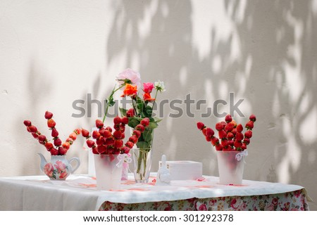 Table decoration, children\'s holiday, wedding, decoration, buffet. Strawberry skewers, roses on the table