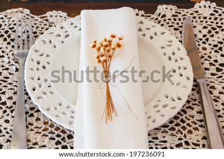 Table decoration: Plate serviette fork knife dried flowers crochet doily. Selective focus