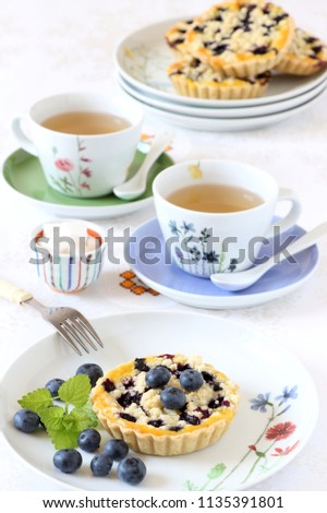 table decoration with blueberry tartelettes and porcelain #1135391801