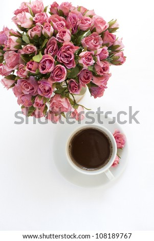 Table decoration with pink roses and cup of coffee