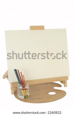 Table easel with blank cream texture canvas board,jar of brushes on a palette