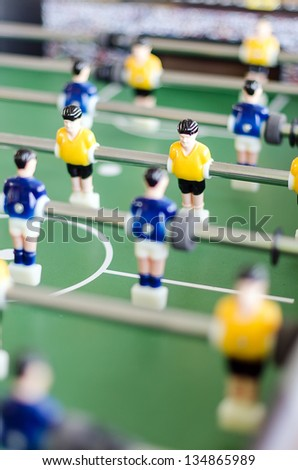 Table football game with yellow and blue players