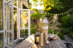 table for lunch outside in the garden in the courtyard with the lights of a country house at sunset. landscape design in the cottage.
