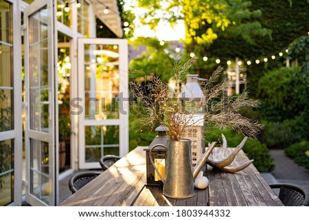 table for lunch outside in the garden in the courtyard with the lights of a country house at sunset. landscape design in the cottage. Foto stock ©