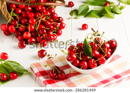 Table full of fresh red cherries, cherries in the bowl and cherries spilled from the basket