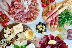 Table full of mediterranean appetizers, tapas or antipasto. Assorted Italian food set. Delicious snack on party or picnic time. Chopping board with meat and cheese. Italian style banquet. Top view.