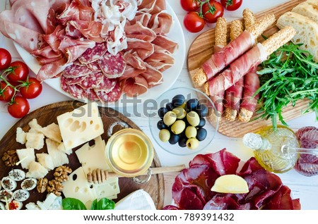 Table full of mediterranean appetizers, tapas or antipasto. Assorted Italian food set. Delicious snack on party or picnic time. Chopping board with meat and cheese. Italian style banquet. Top view. - Shutterstock ID 789391432