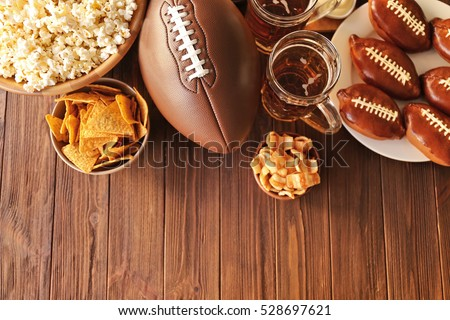 Table full of tasty snacks and beer prepared for watching rugby on TV #528697621