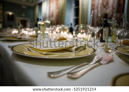table in a luxury restaurant, set for a gala dinner, on the table various candles