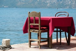 Table in restaurant on the moorage. Restaurant with sea view in Bay of Kotor of the Adriatic Sea, Montenegro