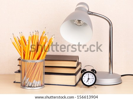 Table lamp with books on desk in room