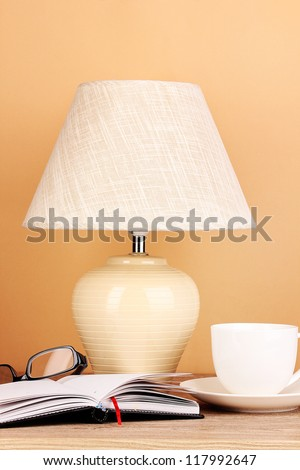 table lamp with cup and glasses on beige background