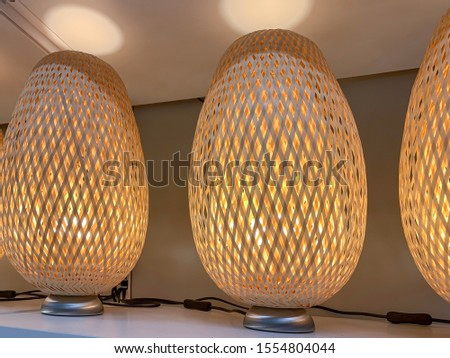 Table lamps with straw wicker lamp shadow standing in a row on a shelf.