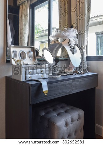 table mirror,sunglasses,jewelry and makeup brushes on a black dressing table