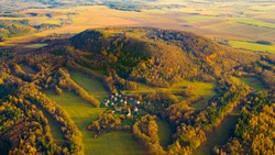 Table Mountain Vladar with hillfort. Famous landmark close to the town Zlutice. Aerial view to ancient monument from bronze age. Autumn landscape in western Bohemia, Czech Republic.