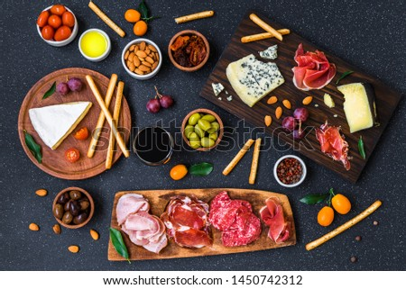 Table of Italian antipasti starters and appetizers with cold meats and cheese delicatessen platter, wine, bread sticks, olives, nuts, and cherry tomatoes