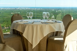 Table of restaurant with country views and Mediterranean sea in background Spain