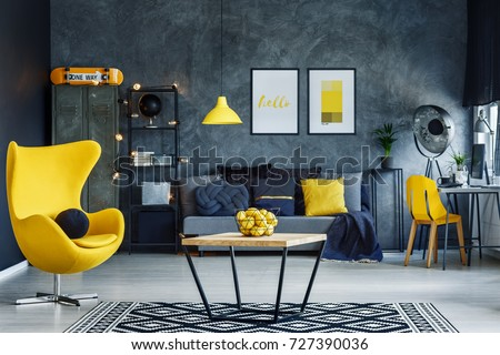 Table on black and white carpet in hygge style living room with designer yellow chair #727390036
