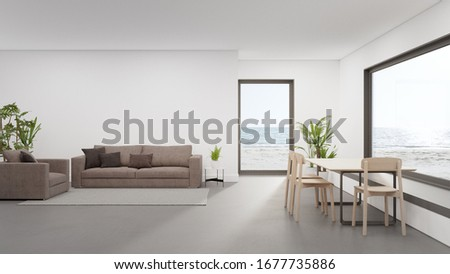 Table on concrete floor of large dining room near living area and sofa in modern beach house or luxury hotel. Minimal home interior 3d rendering with sea view. Сток-фото ©