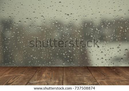 Table on rainy window background