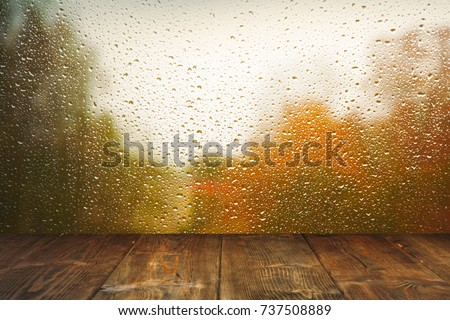 Table on rainy window background