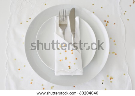 Table place setting with white linen and gold stars for a Christmas theme