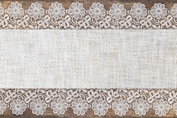Table Runner with Openwork lace  border on brown wooden table rustic background.  Decorative Border Fabric Background, text place, copy space