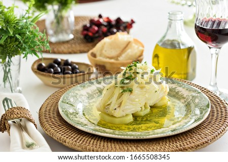 Table set for a dinner, with green decorated portuguese plate, glass of wine and some side dishes. A codfish with potatoes, onion and parsley is being served, an typical portuguese dish. Stock photo ©