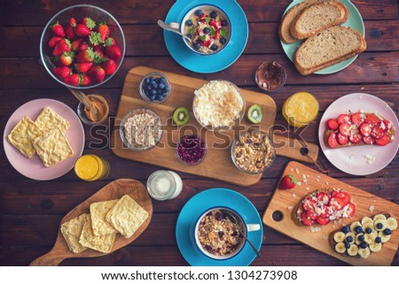 Table set for a healthy breakfast with oatmeal porridge,sweet toast,coconut,peanut butter,chocolate spread,orange juice and fresh berry fruits #1304273908