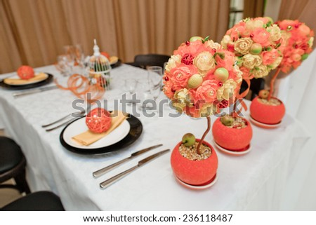 Table set for 4 people. Orange decor and flowers
