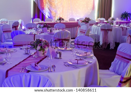 table set for wedding or another catered event dinner - purple light decoration
