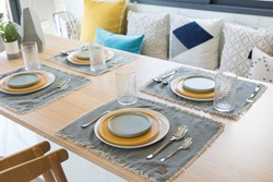 Table set on dinning table with yellow and grey plate setting.