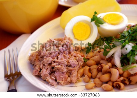 Table set with a plate of tuna salad, boiled egg and potato