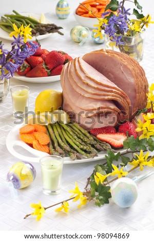 Table set with festive glazed ham for Easter celebration dinner garnished with asparagus, carrots, strawberry, and lemon wedges.