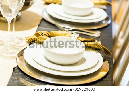Table set with plates and silverware for Holiday dinner.
